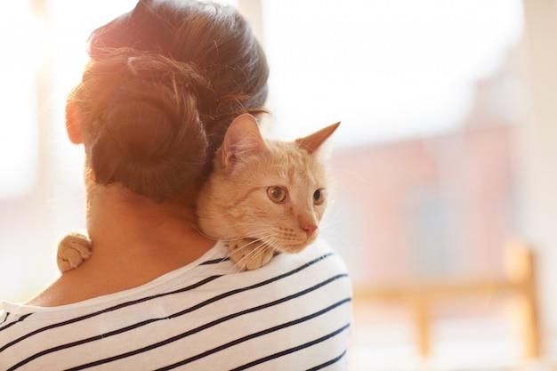 Donna che abbraccia ginger cat back view
