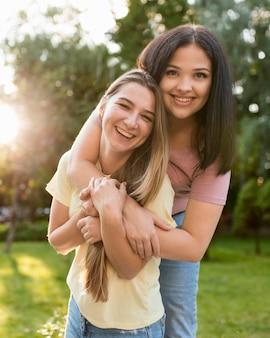 Donna che abbraccia la sua amica da dietro