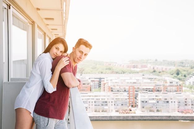 Donna che abbraccia uomo da dietro sul balcone