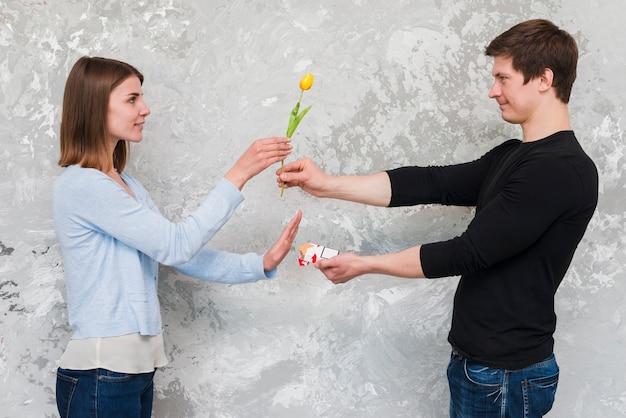 Donna che accetta il fiore giallo del tulipano e no all'offerta del pacchetto della sigaretta dall'uomo bello