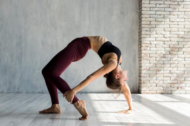 Donna che afferra il suo piede mentre levandosi in piedi in una posa di yoga del ponticello