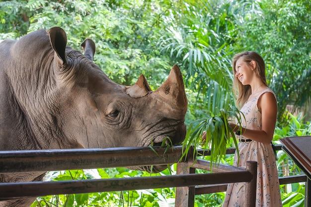 Donna che alimenta il grande rinoceronte
