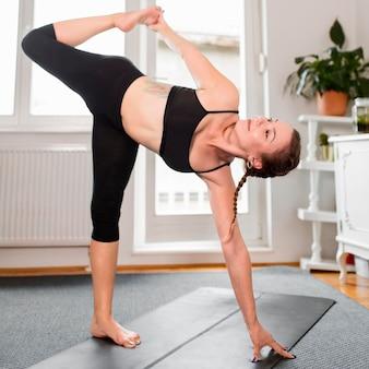 Donna che allunga una gamba sport a casa concetto