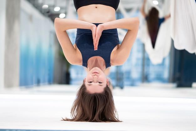 Donna che appende sottosopra in un'amaca. vola lezione di yoga.