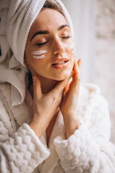 Donna che applica crema per il viso