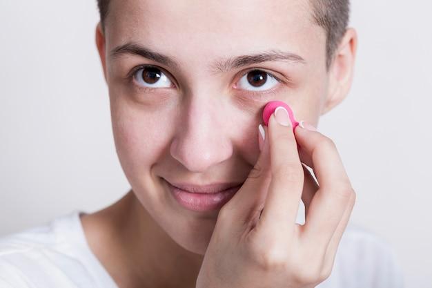 Donna che applica crema per le occhiaie