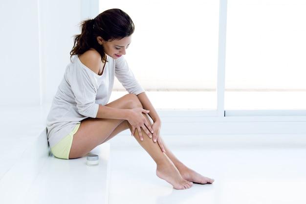 Donna che applica crema sulle gambe