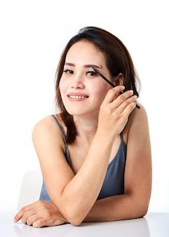 Donna che applica il cosmetico di trucco