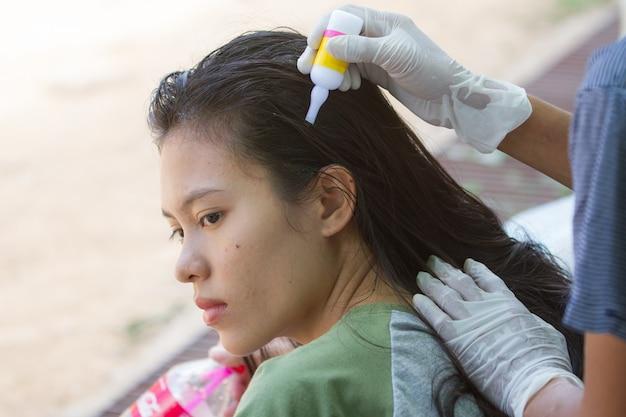 Donna che applica il trattamento di pediculosi a sua figlia
