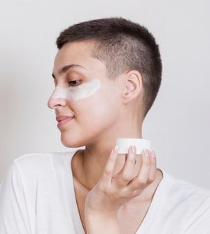 Donna che applica la crema per la cura della pelle del viso