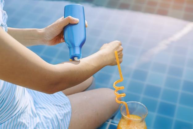 Donna che applica la crema solare, concetto di vacanza estiva