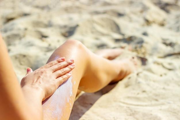 Donna che applica la crema sulle sue gambe abbronzate lisce