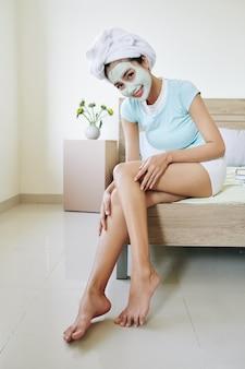 Donna che applica lozione nutriente per il corpo