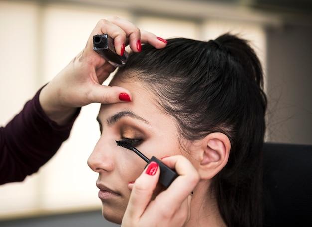 Donna che applica mascara sul modello