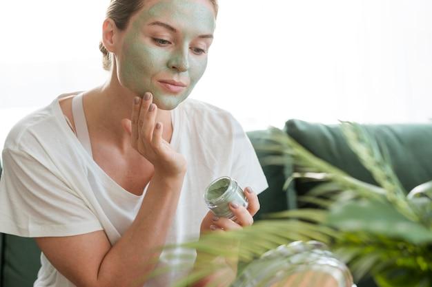 Donna che applica maschera facciale e pianta della casa