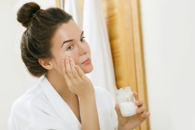 Donna che applica olio di cocco sul suo viso