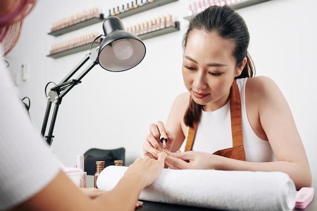 Donna che applica smalto per unghie