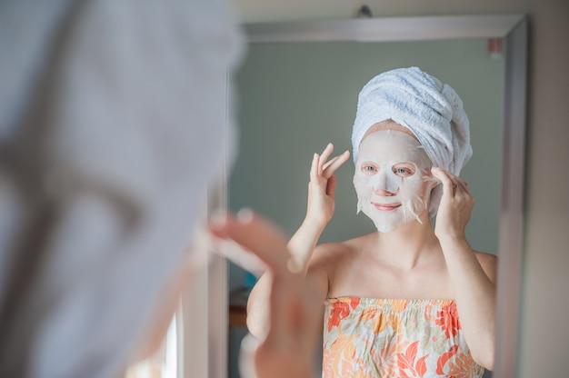 Donna che applica un foglio maschera facciale