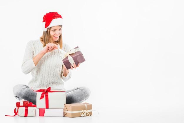 Donna che apre il contenitore di regalo sul pavimento