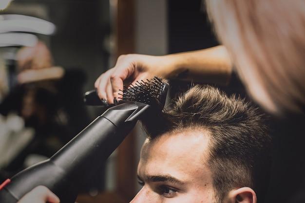Donna che asciuga e acconciatura capelli dell'uomo
