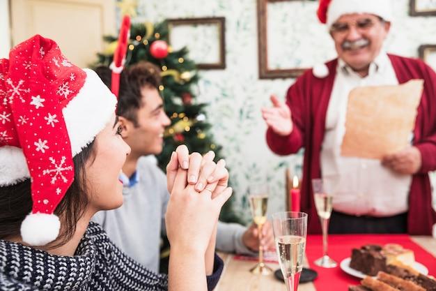 Donna che ascolta il saluto dell'uomo anziano alla tavola festiva