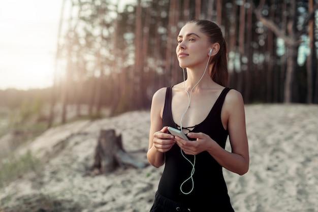 Donna che ascolta l'app del telefono musicale dello smartphone con l'in-ear gear