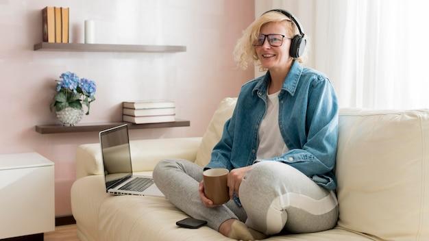 Donna che ascolta la musica e che beve caffè
