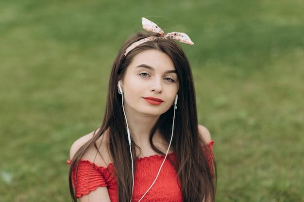 Donna che ascolta la musica. giovane donna che si siede sull'erba verde in parco e che ascolta la musica