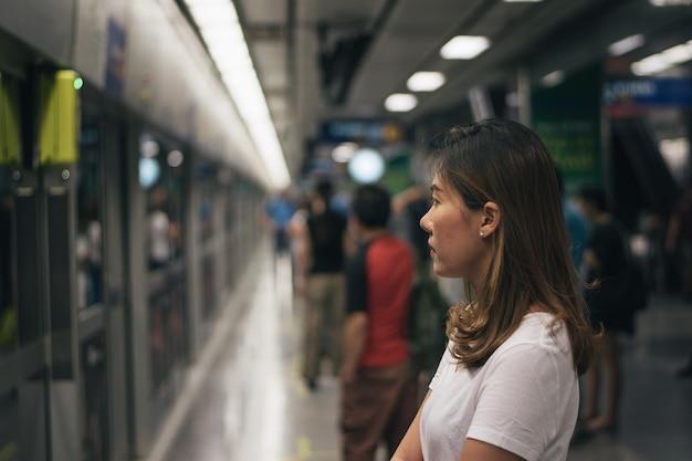 Donna che aspetta sulla piattaforma della stazione e che utilizza lo smart phone alla stazione di collegamento dell'aeroporto