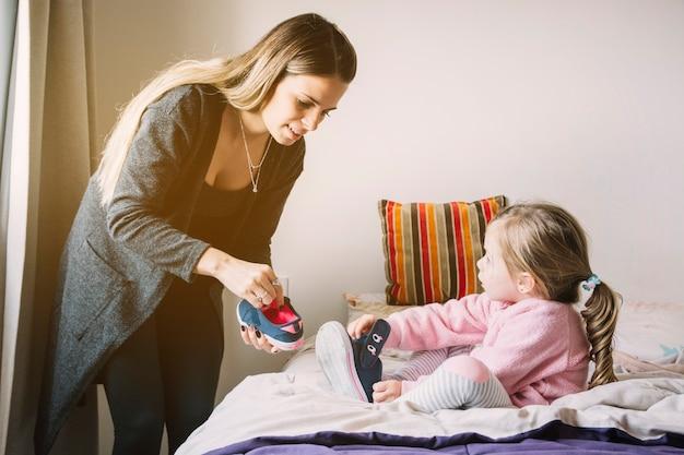 Donna che assiste la figlia mentre indossa le scarpe