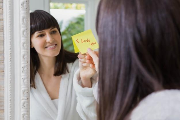 Donna che attacca ti amo parola nota adesiva sullo specchio