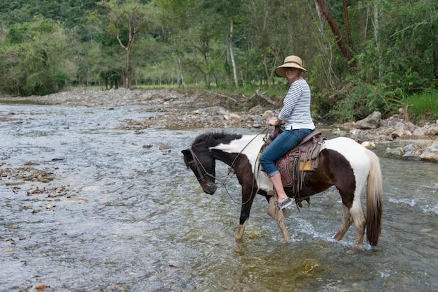 Donna che attraversa un fiume su un cavallo, finca el cisne, honduras