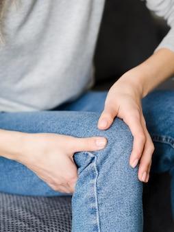 Donna che avverte dolore al ginocchio