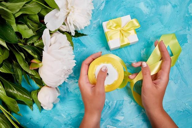 Donna che avvolge il contenitore di regalo bianco con il nastro giallo vicino ai fiori bianchi