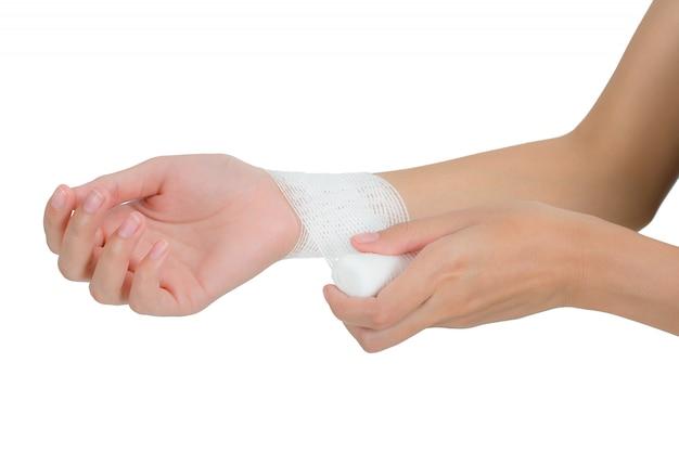 Donna che benda il pronto soccorso il suo polso nell'area di dolore isolata su bianco
