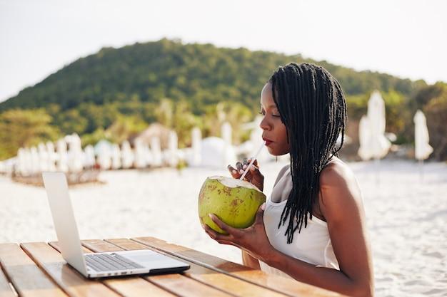 Donna che beve acqua di cocco rinfrescante