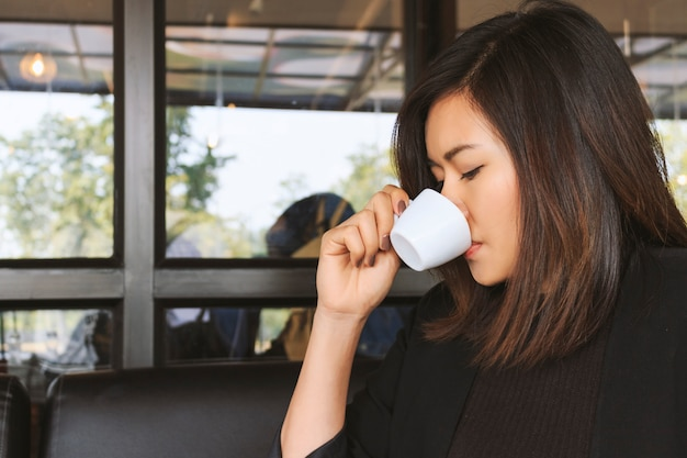 Donna che beve caffè con soft-focus in background.