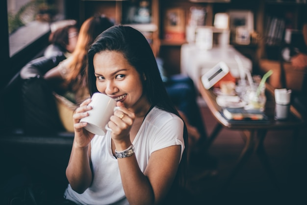 Donna che beve da una tazza di caffè