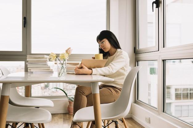 Donna che beve e legge al tavolo