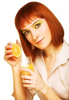Donna che beve fine del succo di arancia in su