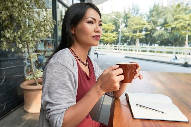 Donna che beve il caffè al bar