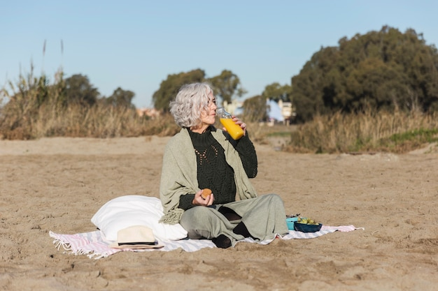 Donna che beve il succo di arancia all'aperto