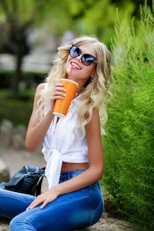 Donna che beve il succo in una calda giornata estiva.