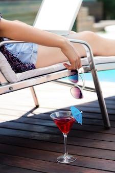 Donna che beve un cocktail e che per mezzo del computer portatile