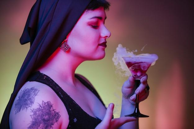 Donna che beve una bevanda spiritosa rossa con un fumo freddo ghiacciato