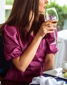 Donna che beve vino al ristorante