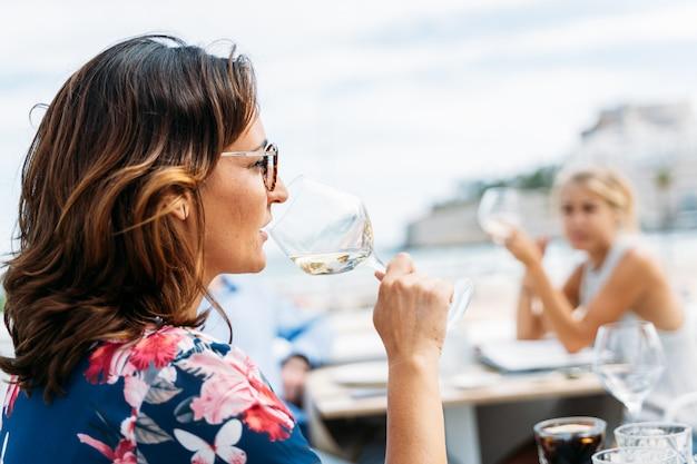 Donna che beve vino con altre persone sulla terrazza di un ristorante sulla spiaggia