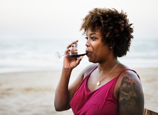 Donna che beve vino sulla spiaggia