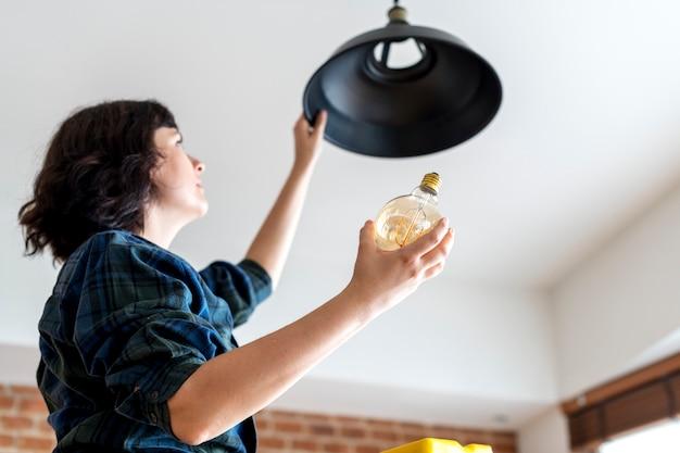 Donna che cambia lampadina