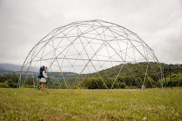Donna che cammina attraverso la costruzione sferica in mezzo al campo